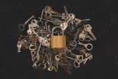 top view of heap different metal keys with lock on black table