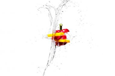 Red and yellow bell pepper slices in water splashes isolated on white stock vector
