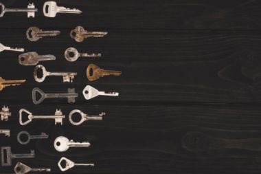 Top view of different vintage keys on black table stock vector