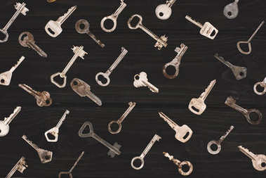 top view of different metal keys on black table
