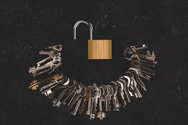 top view of heap different metal keys with opened lock on black table