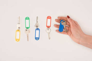 top view of hand holding key beside set of keys with colorful labels isolated on white