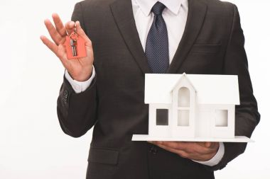 cropped image of man holding maquette of house with key isolated on white