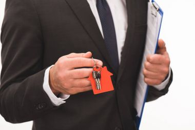 cropped image of man holding contract with key from house isolated on white