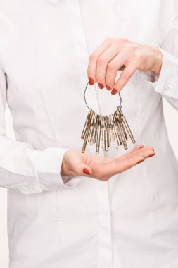 cropped image of female holding keys isolated on white