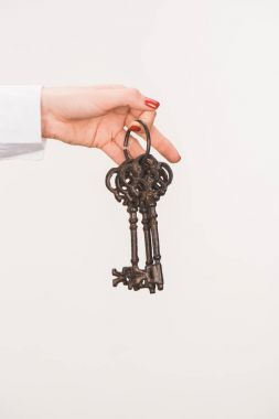 cropped image of female hand holding vintage keys isolated on white