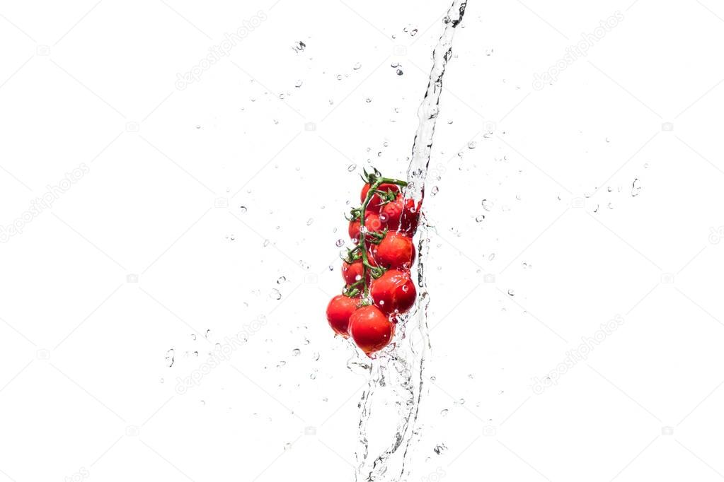 fresh cherry tomatoes in water splashes isolated on white