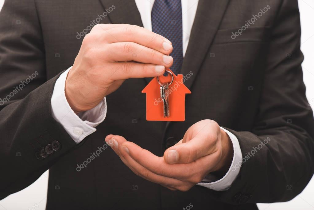 cropped image of man holding key from house isolated on white