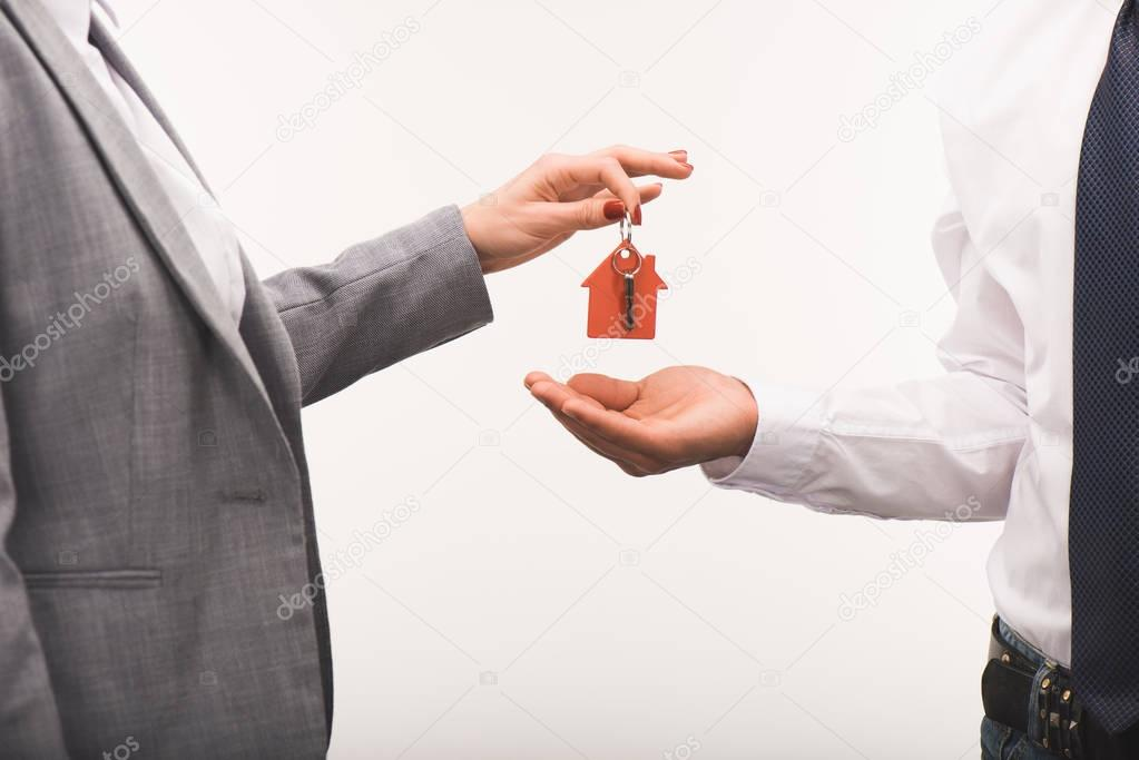 cropped image of woman giving key from house to man isolated on white