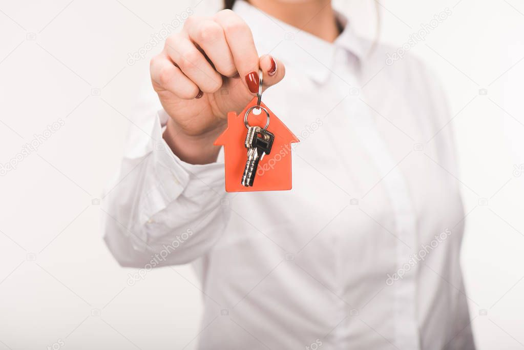 cropped image of female holding key from house isolated on white