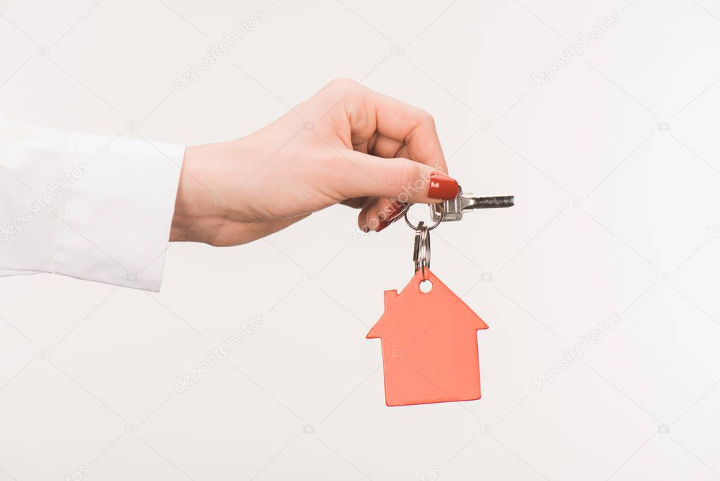 cropped image of female hand holding key from house isolated on white