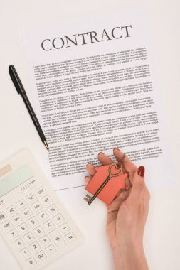 top view of cropped hand holding key from house over contract isolated on white