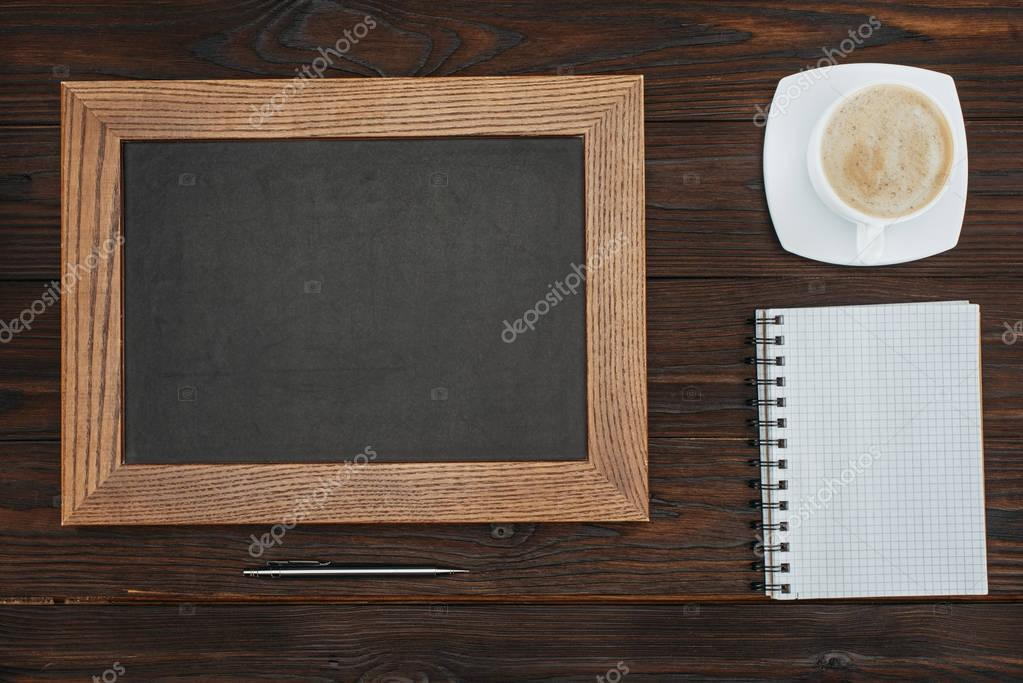 flat lay with empty chalkboard, cup of coffee, blank notebook and pen on dark wooden tabletop