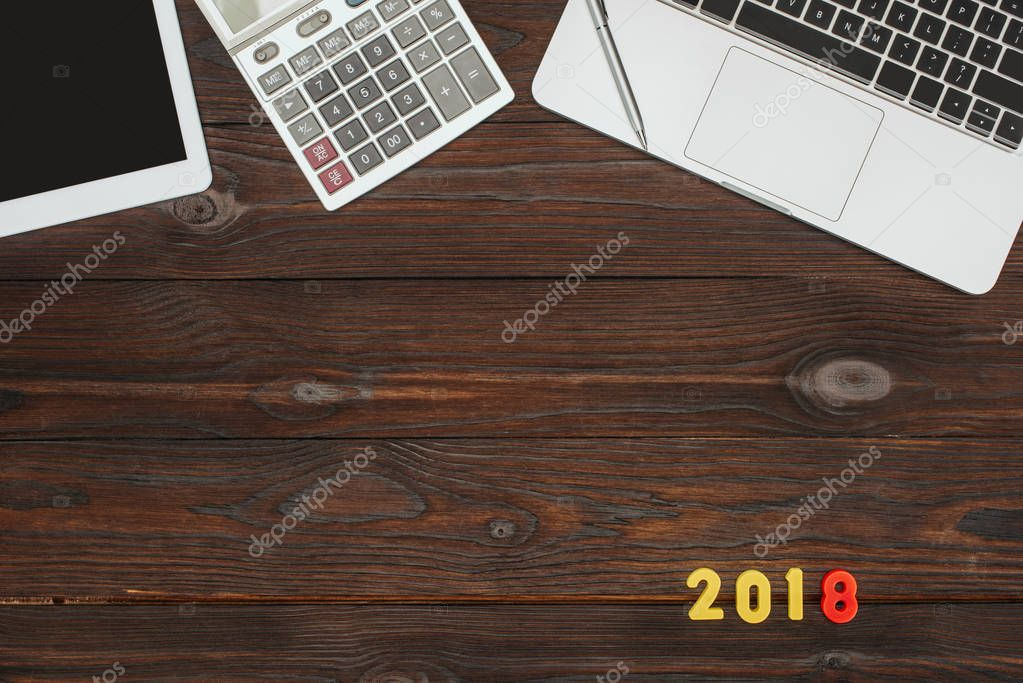 top view of laptop, tablet, calculator and 2018 numbers on wooden tabletop