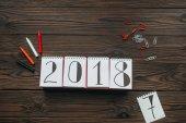ploché s uspořádáním 2018 kalendáře, tužky, piny a klipy na tmavé dřevěné stolní
