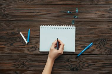 partial view of woman with pencil in hand writing in notebook on wooden tabletop