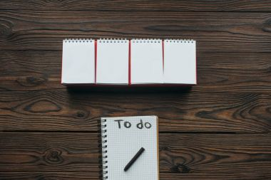 top view of blank calendar and notebook with to do lettering on wooden tabletop