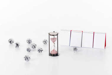 close up view of blank calendar, sand clock and pine cones isolated on white