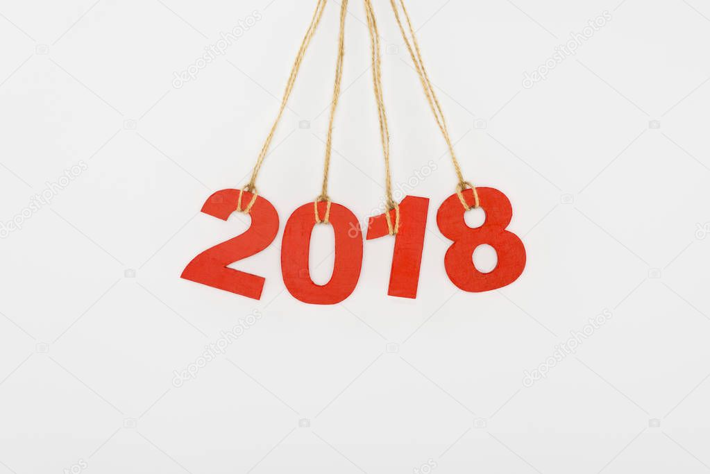 close up view of 2018 year sign hanging on strings isolated on white