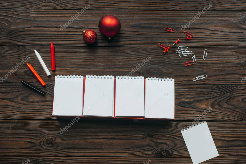 flat lay with blank calendar, pencils and christmas toys on wooden surface