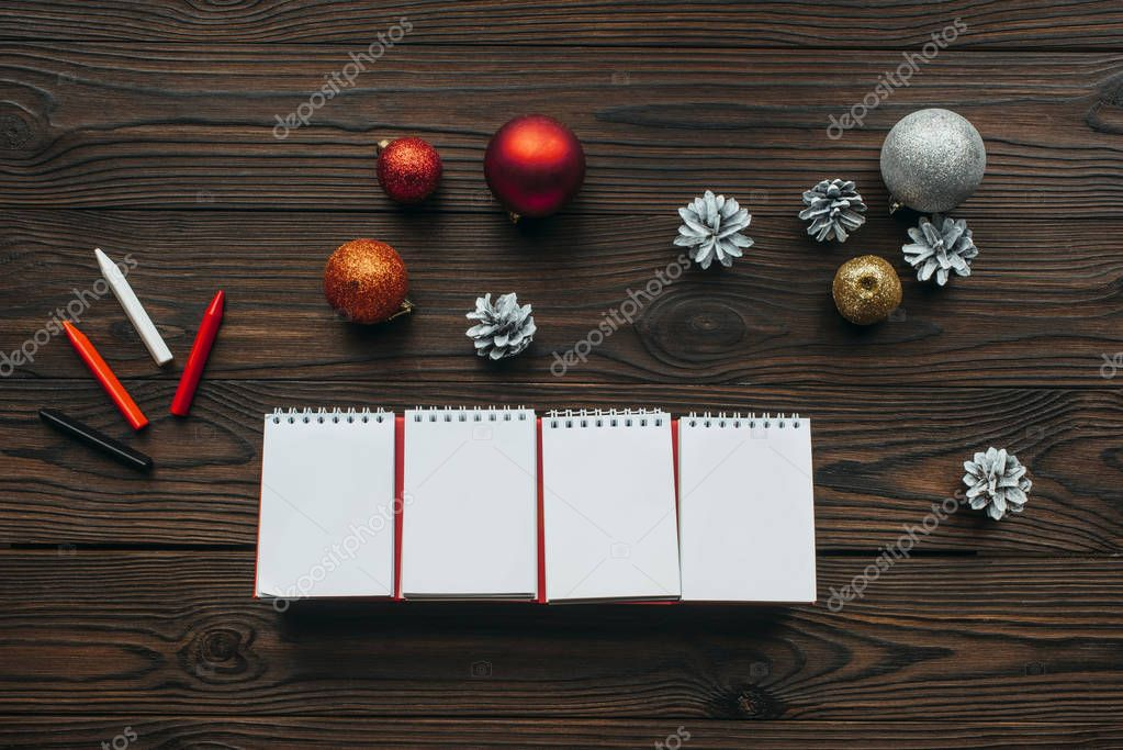 flat lay with blank calendar, pencils, pine cones and christmas toys on wooden surface