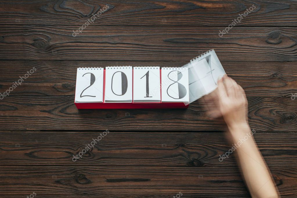 cropped shot of woman tearing calendar paper of 2018 year with dark wooden surface as background
