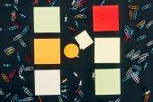 pohled shora bubliny, barevné kancelářské sponky a prázdné poznámky na černém pozadí
