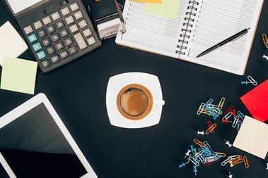 top view of digital tablet with blank screen, cup of coffee, calculator and office supplies on black
