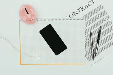 top view of smartphone with blank screen on notebook, contract with pens and piggy bank on white