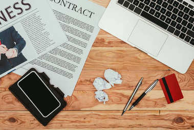 top view of smartphone with blank screen, contract newspaper, laptop and credit card on wooden table