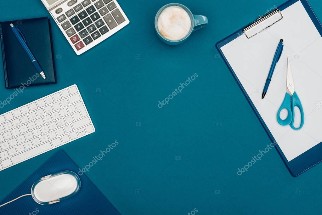 top view of blank clipboard with pen and scissors, computer mouse and keyboard and calculator on blue