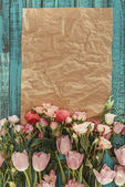 top view of beautiful flowers with craft paper over green wooden background