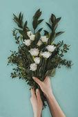 oříznutého obrazu ženských rukou drží kytici s květy eustoma izolované na zelené