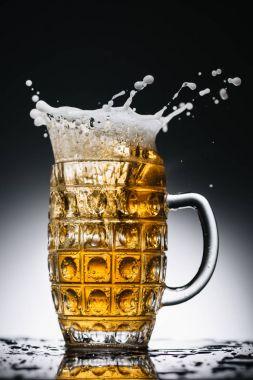 splashes of fresh light beer in glass on black and white