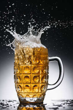 splashes of cold light alcohol beer in mug