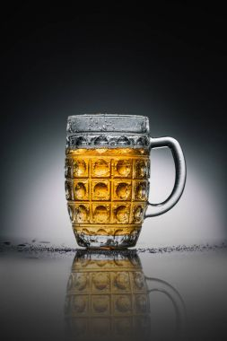 glass with light cold beer on gray reflecting surface