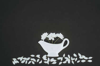 top view of white teapot with daisy flowers over black background