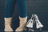 cropped image of woman sitting in warm socks, figure skates on floor