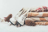 Fotografie white skates with pine cones and stack of blanket and sweater