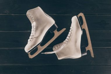 top view of pair of white skates on striped wooden surface