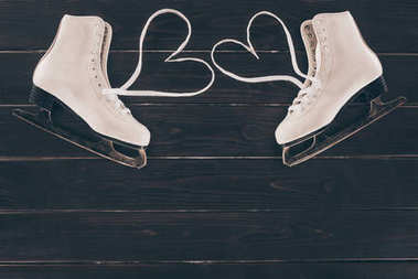 top view of white skates with hearts shaped shoelaces
