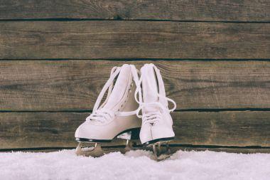 pair of white skates on snow near wooden wall