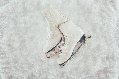 top view of white skates pair on snow