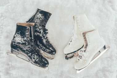 top view of two pairs of white and black skates on snow