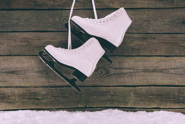 pair of white skates hanging on wooden wall with shoelaces