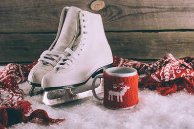 pair of white skates with cup and scarf on snow