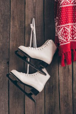pair of white skates and red scarf hanging on wooden wall