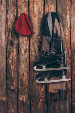 red hat with scarf and black skates hanging on wooden wall