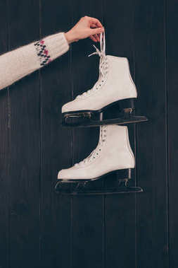 cropped image of woman holding pair of white skates on gray