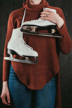 cropped image of woman standing with skates hanging on neck